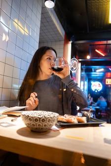 Joven hermosa morena bebe vino en un café