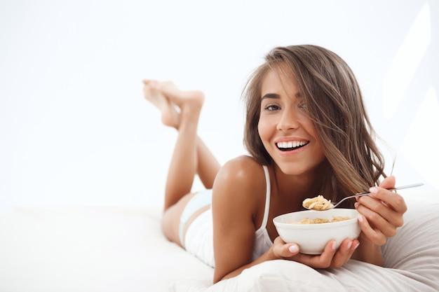Joven hermosa mujer acostada en la cama, desayunando, sonriendo
