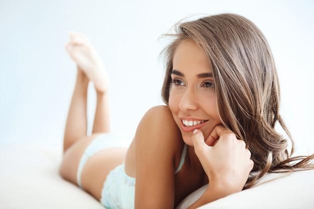 Joven hermosa mujer acostada en la cama temprano en la mañana