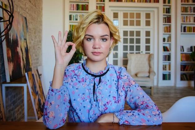 Joven hermosa mujer adolescente muestra signo ok con sus manos