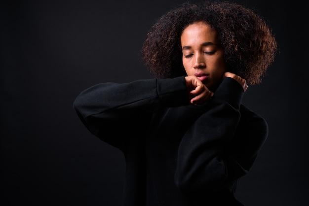Joven hermosa mujer africana con cabello afro sobre negro