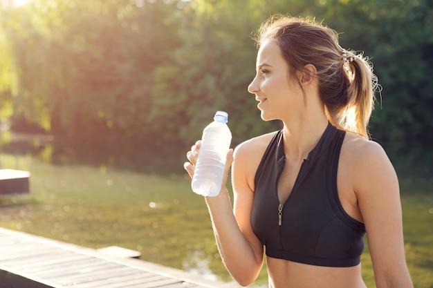 Joven hermosa mujer agua potable durante la mañana para correr en el parque