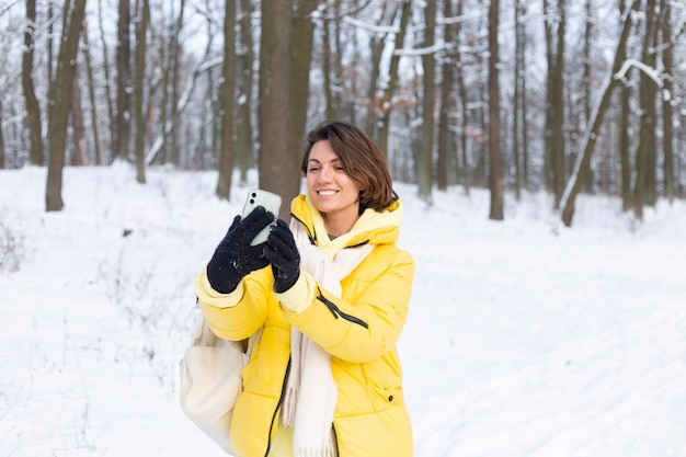 Joven hermosa mujer alegre feliz en el video blog del bosque de invierno, hace una foto selfie
