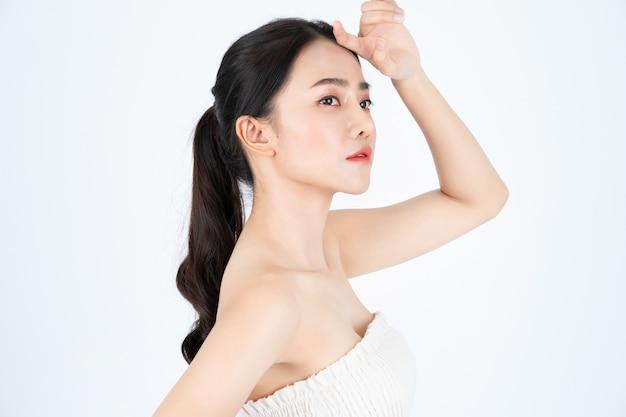 Joven hermosa mujer asiática en camiseta blanca, tiene una piel sana y brillante.
