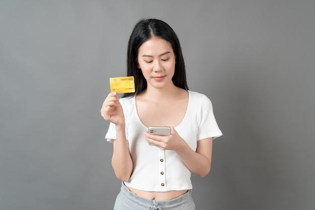 Joven hermosa mujer asiática con cara feliz y presentando tarjeta de crédito en la mano mostrando confianza y seguridad para realizar el pago