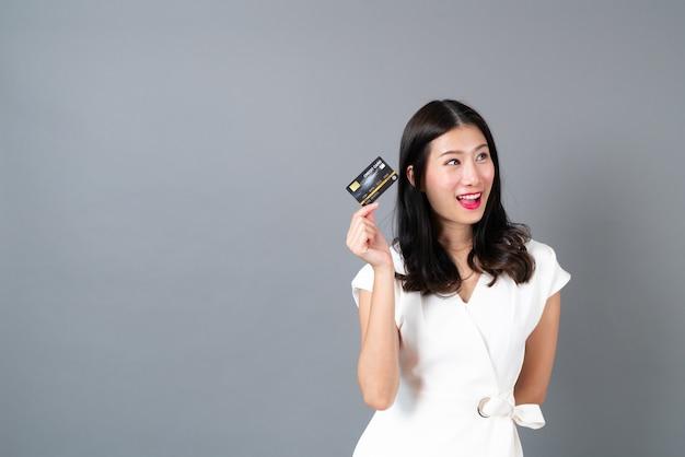 Joven hermosa mujer asiática con rostro emocionante y sonriente y presentando tarjeta de crédito en la mano mostrando confianza y seguridad para realizar el pago en la pared gris