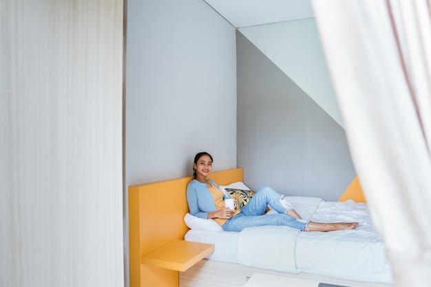Joven hermosa mujer asiática tomando un café en el acogedor dormitorio