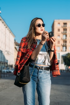 Joven hermosa mujer asiática visitando la ciudad al aire libre con cámara