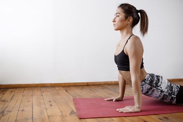 Joven hermosa mujer atlética practicando yoga interior en alfombra roja