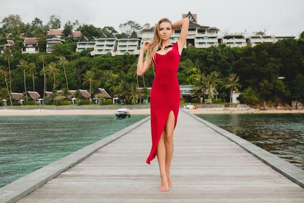 Joven hermosa mujer atractiva sola en el muelle en el hotel resort de lujo, vacaciones de verano, vestido largo rojo, cabello rubio, ropa sexy, playa tropical, seductora, sensual, sonriente