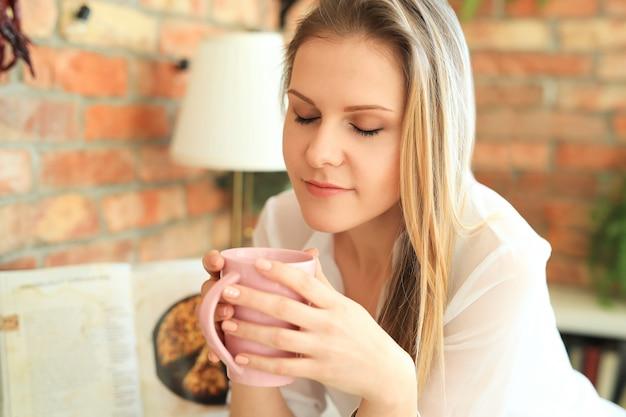 Joven hermosa mujer bebiendo café o té