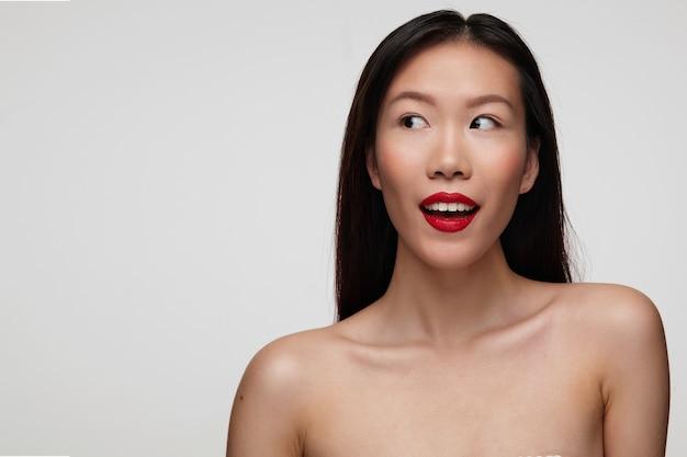 Joven hermosa mujer de cabello oscuro con labios rojos mirando con entusiasmo a un lado y manteniendo la boca abierta, de pie contra la pared blanca