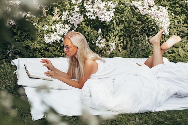 Joven hermosa mujer de cabello rubio tendido sobre una manta en el césped y libro de lectura