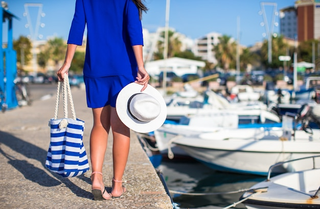 Joven hermosa mujer caminando con sombrero y bolsa en el muelle cerca del barco