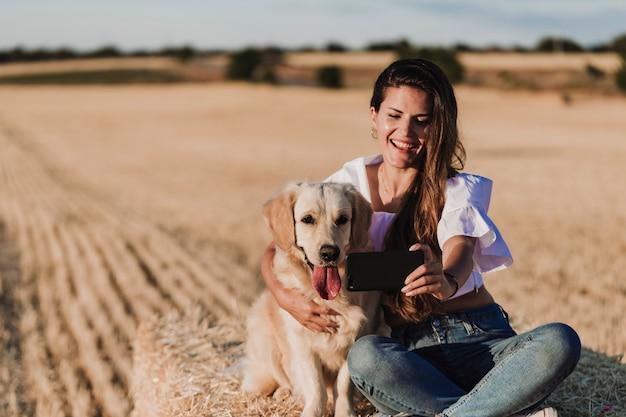 Joven hermosa mujer caminando con su perro golden retriever en un campo amarillo al atardecer