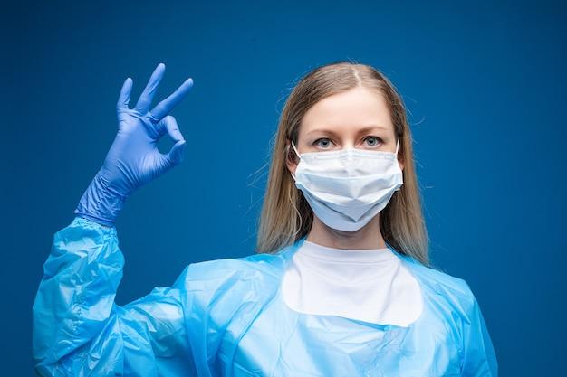 Joven hermosa mujer caucásica en bata médica azul y con máscara médica blanca en su rostro mira a la cámara y muestra ok