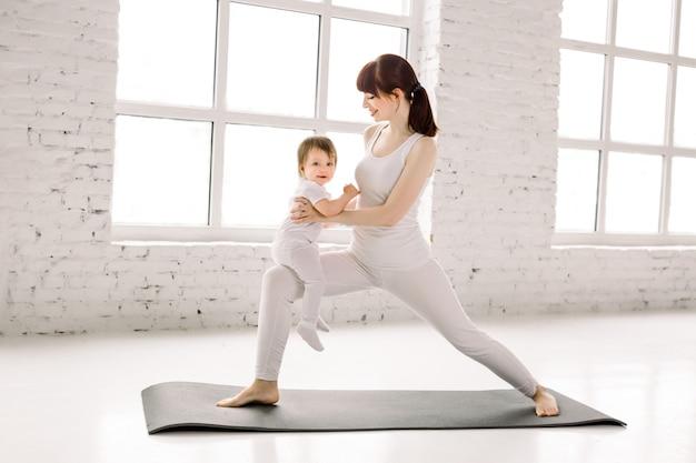 Joven hermosa mujer caucásica haciendo ejercicio físico en el gimnasio de luz grande con su niña niño juntos. aptitud maternidad y maternidad