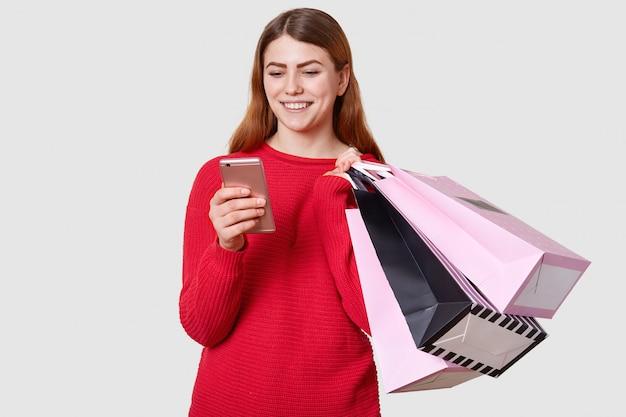 Joven hermosa mujer caucásica de moda tiene bolsas de compras en una mano y teléfono inteligente en otro aislado en blanco