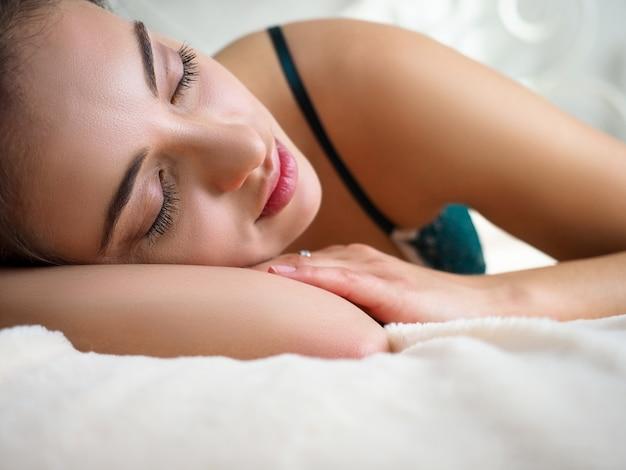 Joven hermosa mujer caucásica tomando una siesta pacífica sola en su día libre en la habitación de la casa
