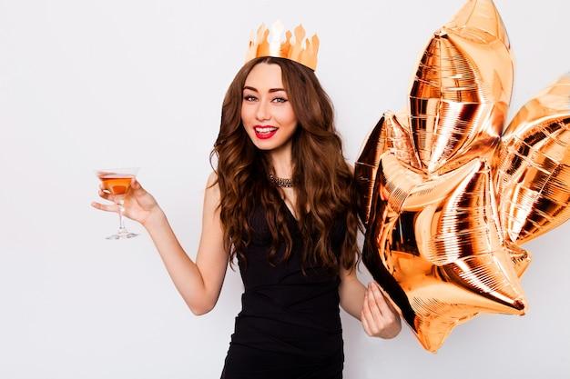 Joven hermosa mujer celebrando en vestido negro sonrisa y posando con cóctel en mano y globos de pureza.