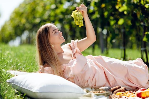 Joven hermosa mujer come uvas frescas en un jardín de uvas