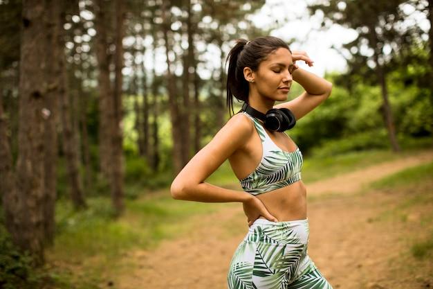 Joven hermosa mujer corredor escuchando música y tomando un descanso después de trotar en un bosque