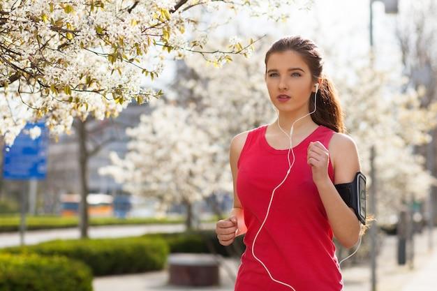Joven hermosa mujer corriendo en la ciudad