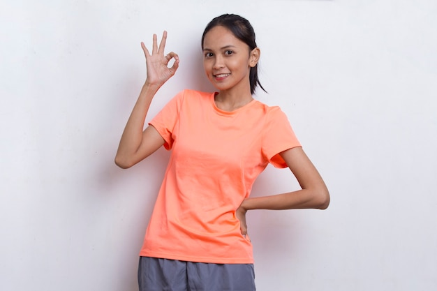 Joven hermosa mujer deportiva asiática mostrando un pulgar hacia arriba gesto ok sobre fondo blanco.