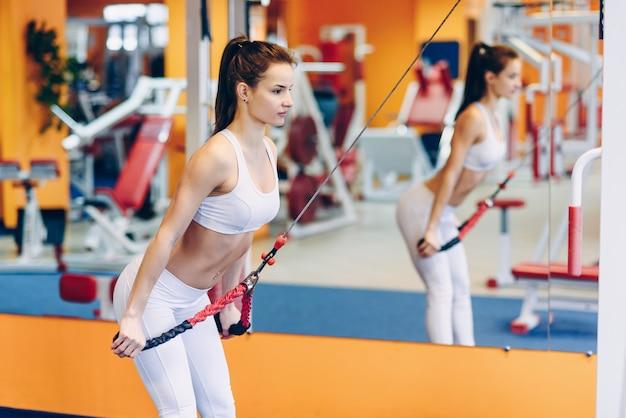 Joven hermosa mujer deportiva haciendo ejercicios en un gimnasio