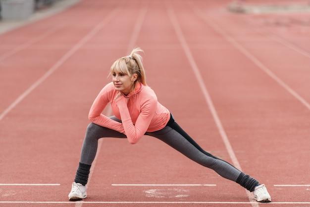 Joven hermosa mujer deportiva rubia sonriente estirando la pierna y calentando en la pista antes de correr.
