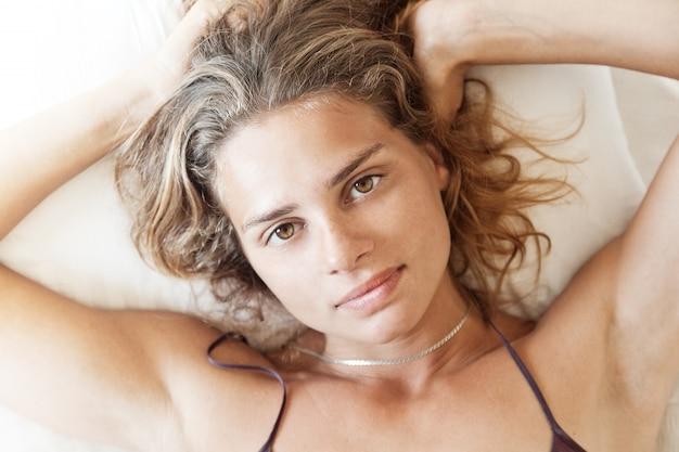 Joven hermosa mujer despertando en la cama, retrato de primer plano