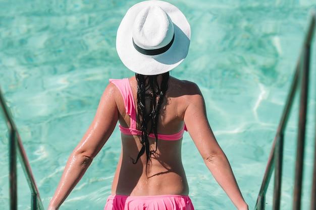 Joven hermosa mujer disfrutando de la lujosa piscina tranquila