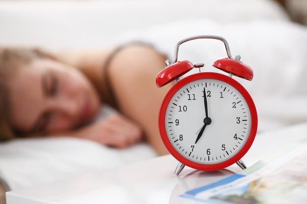 Joven hermosa mujer duerme bien en la alarma de la mañana