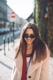 Joven hermosa mujer elegante caminando en abrigo rosa