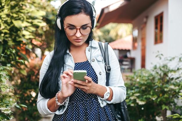Joven hermosa mujer elegante con smartphone, auriculares, gafas, verano, traje de mezclilla vintage, sonriente, feliz, positivo