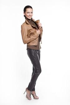 Joven hermosa mujer elegante sonriente sexy en chaqueta marrón aislada en blanco de cuerpo entero