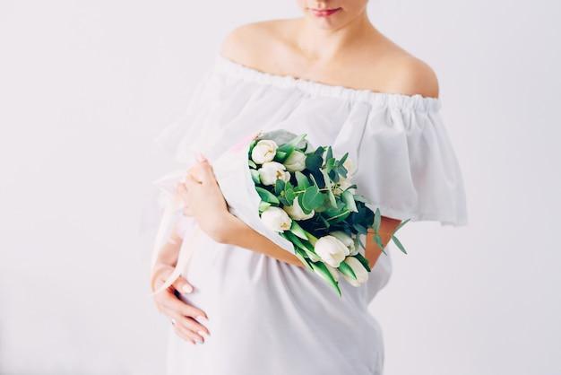 Joven hermosa mujer embarazada en un vestido blanco con un ramo de tulipanes blancos