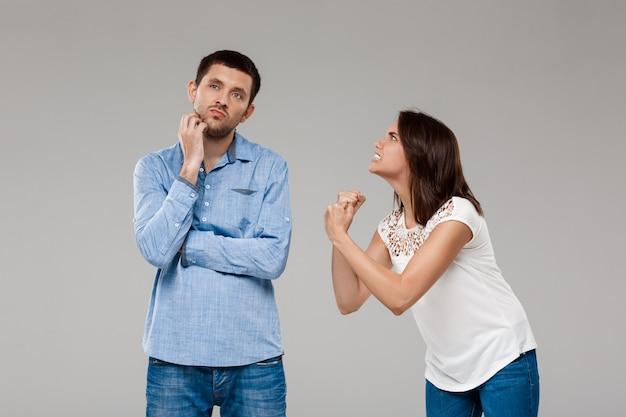 Joven hermosa mujer enojada con hombre sobre pared gris