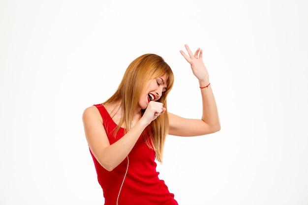 Joven hermosa mujer escuchando música en auriculares y cantando sobre pared blanca