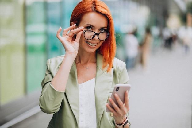 Joven hermosa mujer exitosa en traje verde hablando por teléfono