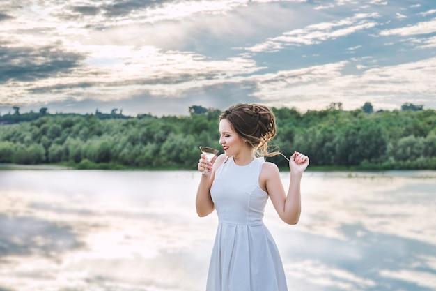 Joven hermosa mujer feliz en vestido blanco celebra despedida de soltera en el muelle