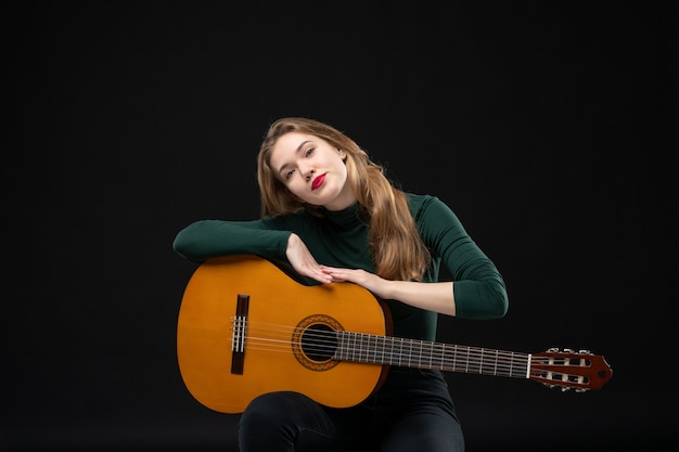Joven hermosa mujer guitarrista sosteniendo su instrumento musical favorito en la oscuridad