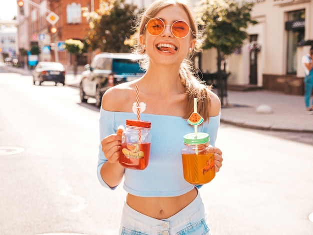 Joven hermosa mujer hipster sonriente en gafas de sol.