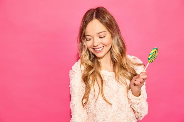 Joven hermosa mujer hipster sonriente en ropa de moda de verano. mujer despreocupada atractiva que presenta cerca de la pared rosada. modelo positivo comiendo piruleta