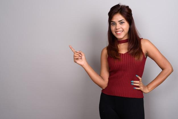 Joven hermosa mujer india contra la pared gris