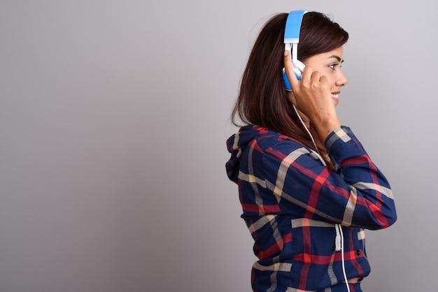 Joven hermosa mujer india escuchando música contra la pared gris