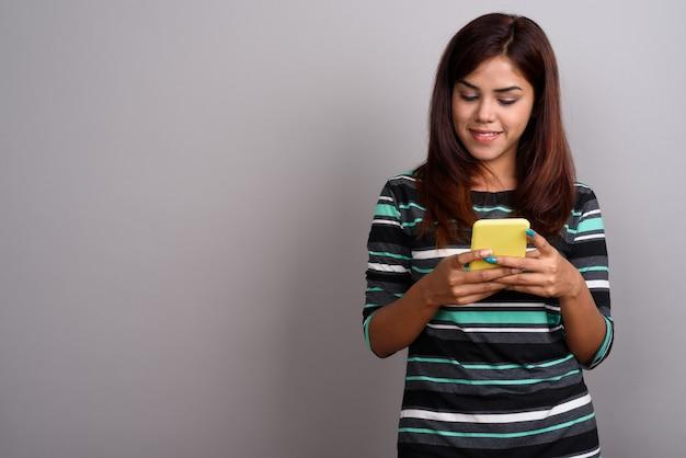 Joven hermosa mujer india mediante teléfono móvil contra la pared gris