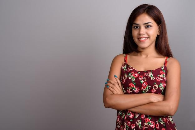 Joven hermosa mujer india con vestido contra la pared gris