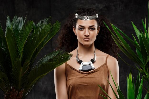 Joven hermosa mujer morena en plantas tropicales sobre pared gris