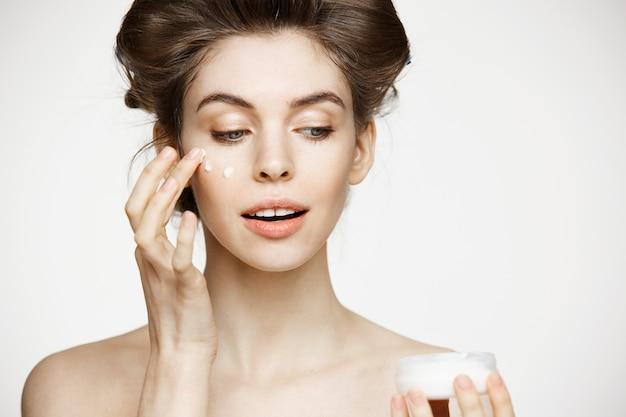 Joven hermosa mujer morena en rizadores para el cabello sonriente batiendo la cara. tratamiento facial. salud estética y cosmetología.